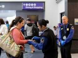 TSA agents screen a passenger at San Francisco International Airport in San Francisco, California, February 27, 2015