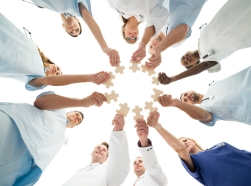 Directly below shot of medical team joining jigsaw pieces in huddle