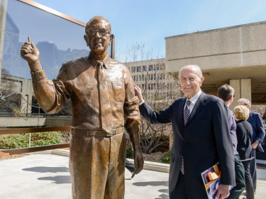 Dr. Donald Seldin poses with a statue in his likeness at the Dr. Donald Seldin Plaza