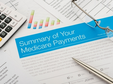 Medicare payments summary with paperwork, photo by courtneyk/Getty Images