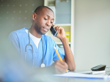 Doctor speaking on the phone, photo by sturti/Getty Images