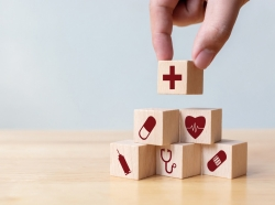 Hand stacking blocks with medical icons, photo by marchmeena29/Getty Images