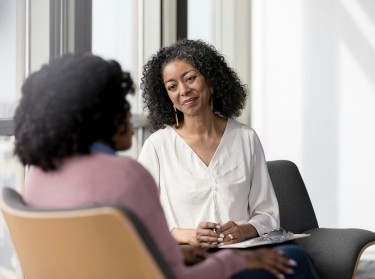 A therapist listens to a patient, photo by SDI Productions/Getty Images