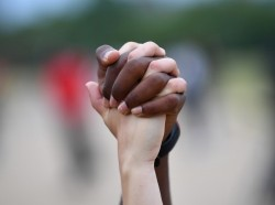 A man and a woman hold hands aloft during a Black Lives Matter protest in Hyde Park, London, June 3, 2020, photo by Dylan Martinez/Reuters