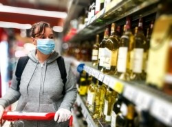 Woman with a shopping cart wearing a mask and gloves in the alcohol aisle at the grocery store, photo by coldsnowstorm/Getty Images