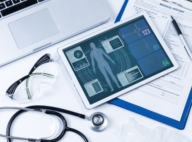Vital sign monitor in tablet PC, with laptop and stethoscope, photo by metamorworks/Getty Images