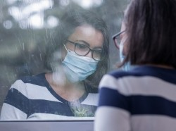 Woman wearing a face mask looks out a window in the rain, photo by FerreiraSilva/Getty Images