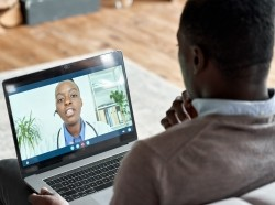 Male black patient on conference video call with female Black doctor, photo by insta_photos/Getty Images