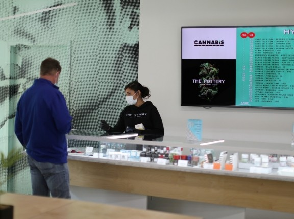 Ashlee Mason, 26, serves a customer at The Pottery Cannabis Dispensary, as marijuana deliveries increase amid the spread of COVID-19, in Los Angeles, California, April 14, 2020, photo  by Lucy Nicholson/Reuters