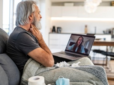 Man talking on telemedicine with doctor, photo by AzmanJaka/Getty Images