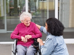 Senior woman in wheelchair with caregiver, photo by SilviaJansen/Getty Images