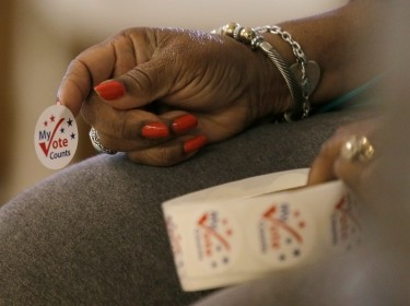 A worker holds stickers for voters at a polling station at the Princeton Baptist Church during the U.S. presidential election, in Princeton, North Carolina, November 8, 2016, photo by Chris Keane/Reuters