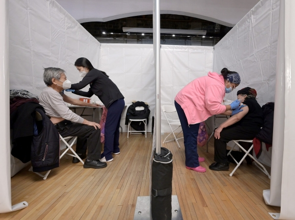 An elderly married couple receive the COVID-19 vaccine at the same time inside the Korean Community Services center in the Queens borough of New York City, New York, February 11, 2021, photo by Anthony Behar/Reuters