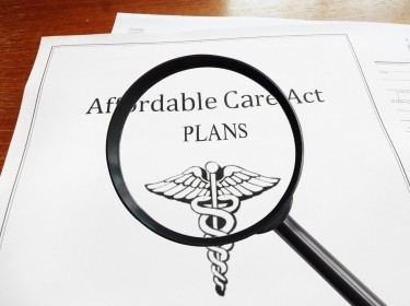 Magnifying glass over papers titled Affordable Care Cat Plans, photo by zimmytws/Getty Images