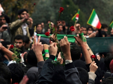 Students show victory signs and red roses during protests in central Tehran December 7, 2009