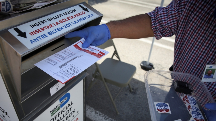 A poll worker casts a mail-in ballot for a voter at a drive-thru polling station during the primary election amid the COVID-19 outbreak in Miami, Florida, August 18, 2020, photo by Marco Bello/Reuters