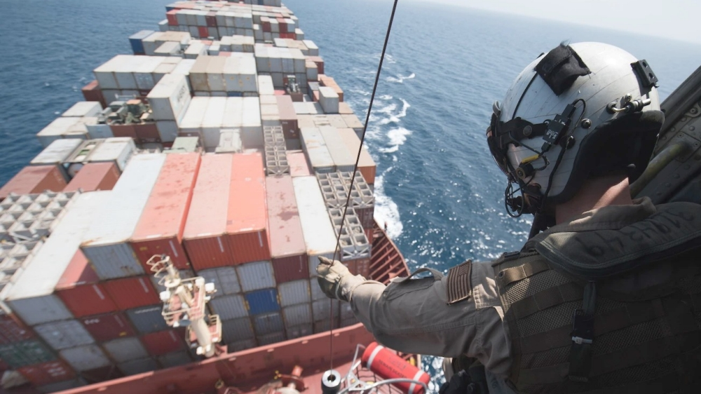 A U.S. Naval Air Crewman lowers a litter onto the deck of a merchant ship in the Gulf of Aden
