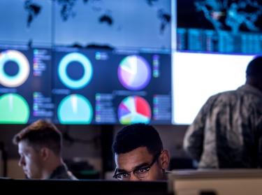 U.S. cyber warfare operators lit from below by computer screens