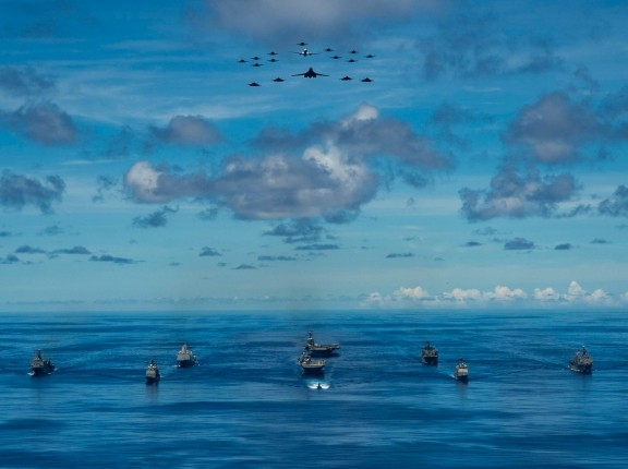 Eleven U.S. vessels steam in formation while U.S. Navy and Department of the Air Force aircraft fly overhead during the Valiant Shield 2020 exercise