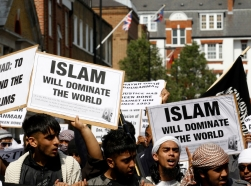 Muslims hold placards as they march towards the U.S. embassy in London, May 2011