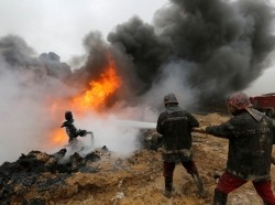 Firefighters put out fires at oil wells that were set ablaze by Islamic State militants before they fled the oil-producing region of Qayyara, Iraq, January 28, 2017