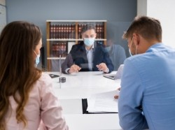 A lawyer consulting with a man and a woman, all wearing face masks to protect against spread of COVID-19. Photo by Andrey Popov / Adobe Stock