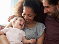 Parents on sofa cuddling baby daughter