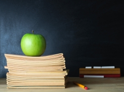 An apple sits on a stack of booklets on a teacher's desk