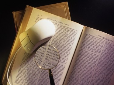 Mouse and magnifying glass on book