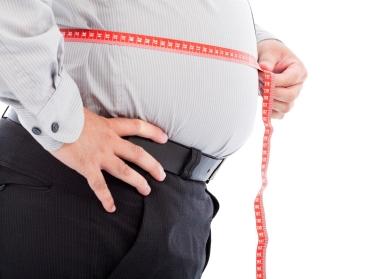 An obese man measuring his abdomen