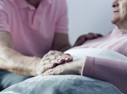 A senior man holding his dying wife's hand
