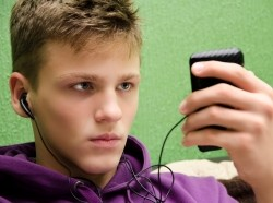 Teenage boy with headphones, looking at a handheld device and listening to music