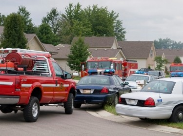 Fire trucks and police cars in a residential neighborhood responding to a an emergency situation