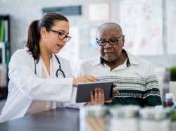 Female doctor consulting with older male patient, using a tablet to demonstrate