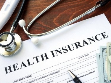 Stethoscope, thermometer, money, and pen surrounding a health insurance application