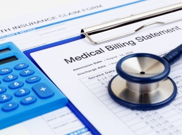 Calculator, medical billing statement on a clipboard, and stethoscope