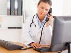 Doctor on the phone looking at a computer monitor