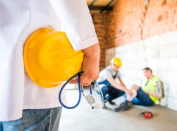 Man in foreground holding a hard hat and stethoscope with another worker assisting an injured worker in the background