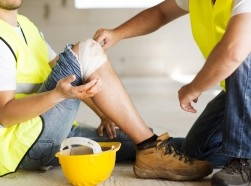 A construction worker getting his knee bandaged onsite