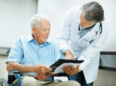 Doctor showing documents to man in wheelchair