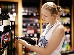 Woman reading inscription on the wine bottle in store