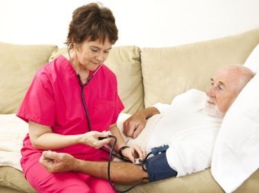 A home health nurse checking man's blood pr