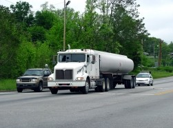 A tanker truck on the road with two cars