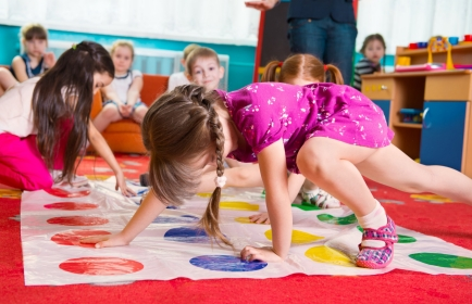 Young children play Twister in the classrom