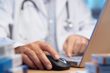 A doctor uses his computer