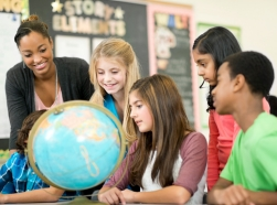 A group of children study the globe with their teacher