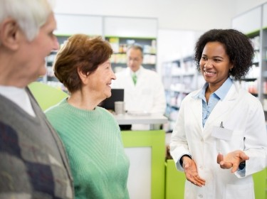An older couple talking with a pharmacist