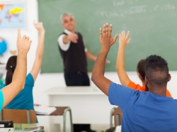 A gorup of students with hands up in the classroom