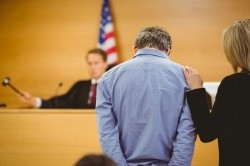 A man and his lawyer hear a ruling from a judge