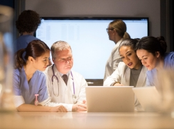 Medical personnel gathered around a laptop